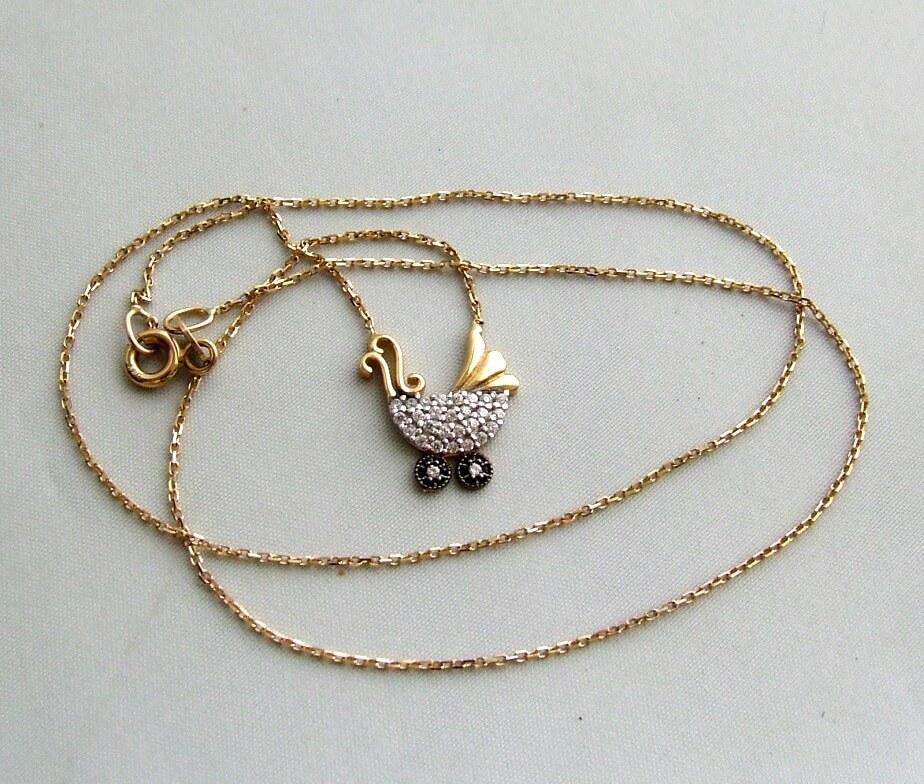 Gouden collier met kinderwagen hanger