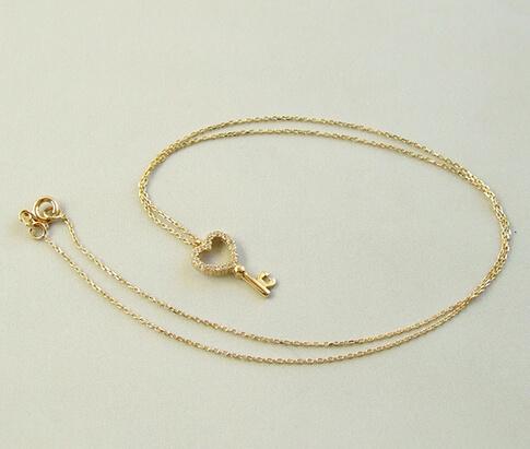 Gouden collier en zirkonia harten sleutelhanger